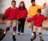 Adults walking and children on rollerblades