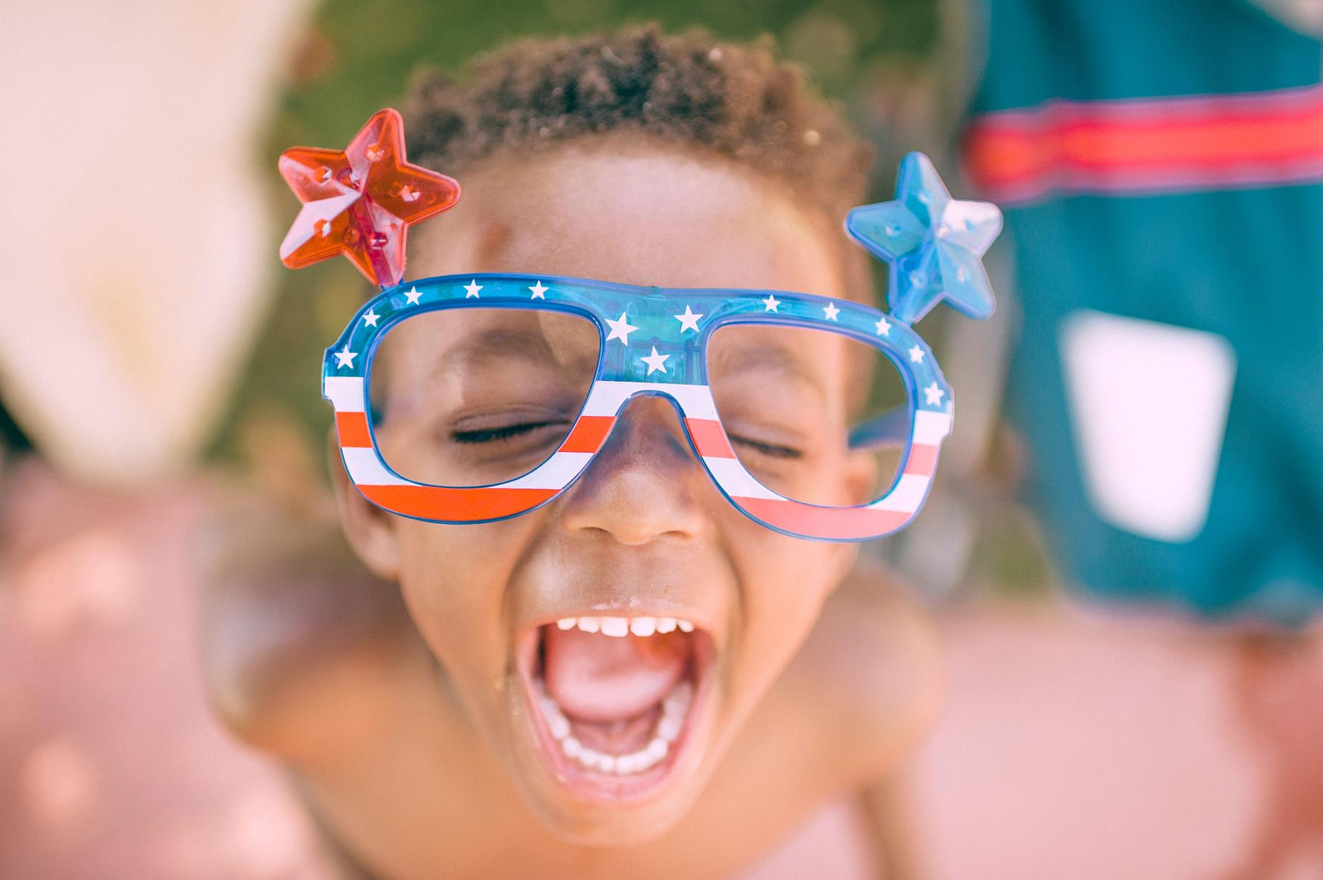boy wearing red, white and blue sunglasses