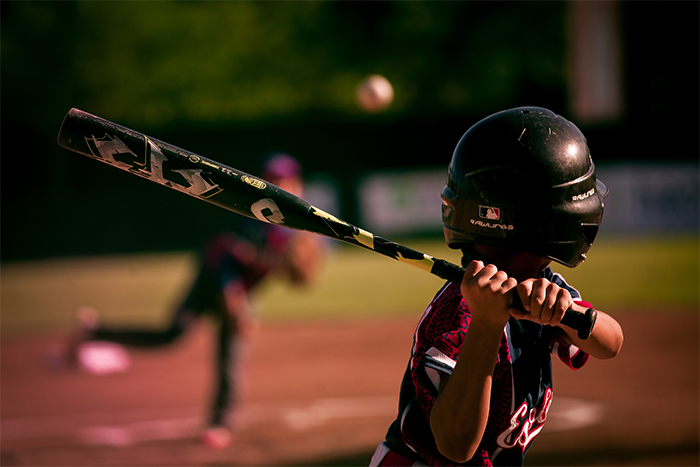 youth baseball player swinging baseball bat