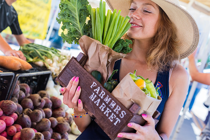 Woman holding fresh produce at farmers market