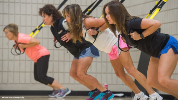 women hanging on TRX straps in fitness class