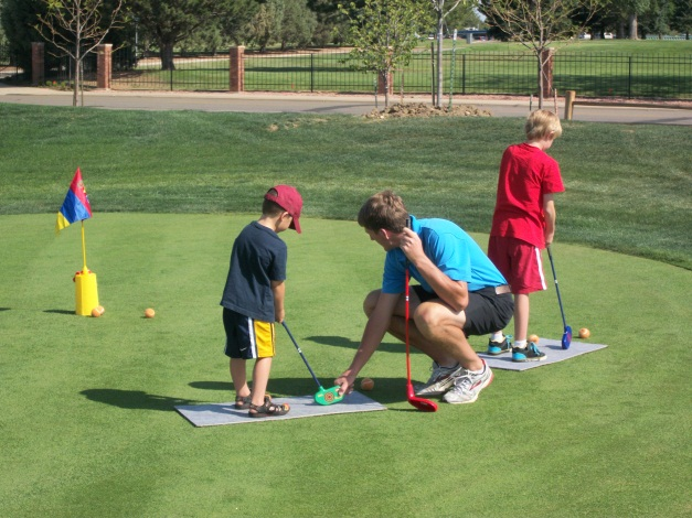 boys learning to putt on putting green
